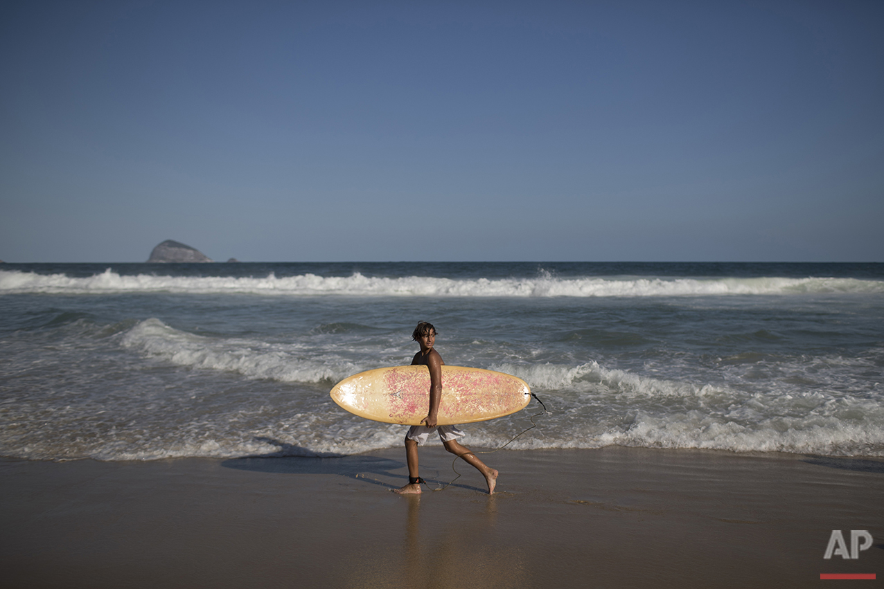 Eric Marques walks along the shore of Sao Conrado beach during his surf class in Rio de Janeiro, Brazil, Saturday, Aug. 13, 2016. Although it's known as a top surfing spot, the sewage-filled Sao Conrado beach was removed from the list of venues from a surfing competition earlier this year due to pollution. (AP Photo/Felipe Dana)