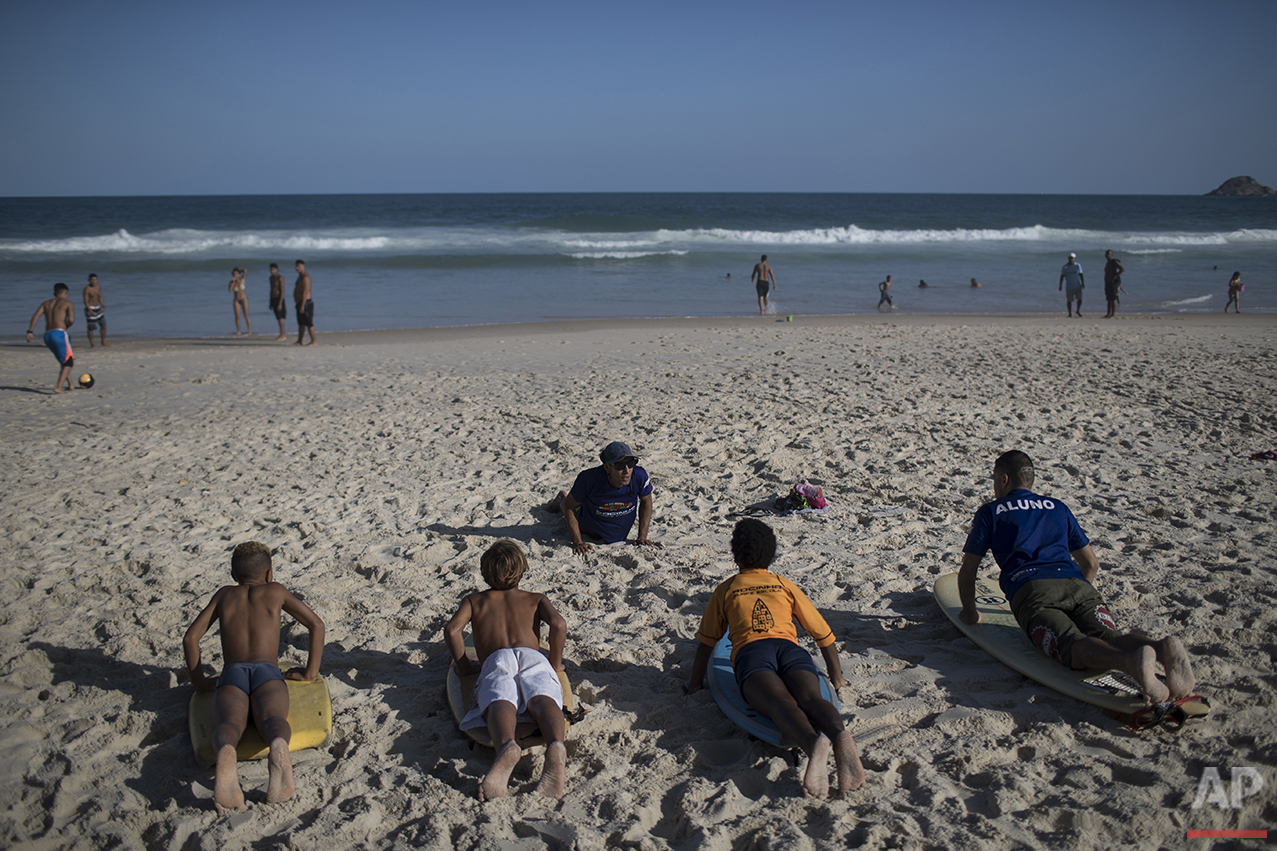 Ricardo Ramos, top, founder of the Rocinha Surf School, gives a lesson to his students on Sao Conrado beach in Rio de Janeiro, Brazil, Saturday, Aug. 13, 2016. Ramos' idea is to teach impoverished children and adults with special disabilities to surf at the foot of the slum to keep them away from drugs and violence. (AP Photo/Felipe Dana)