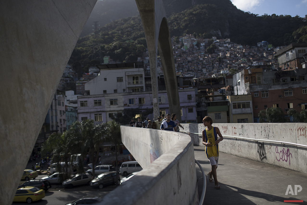 Eric Marques crosses a pedestrian bridge in the Rocinha slum on his way to the Rocinha Surf School near Sao Conrado beach in Rio de Janeiro, Brazil, Saturday, Aug. 13, 2016. Rocinha has been part of a pacification program aimed at making Rio safer ahead of the Olympic Games. But heavily-armed drug dealers still plague its alleys and deadly gun battles often break out. (AP Photo/Felipe Dana)