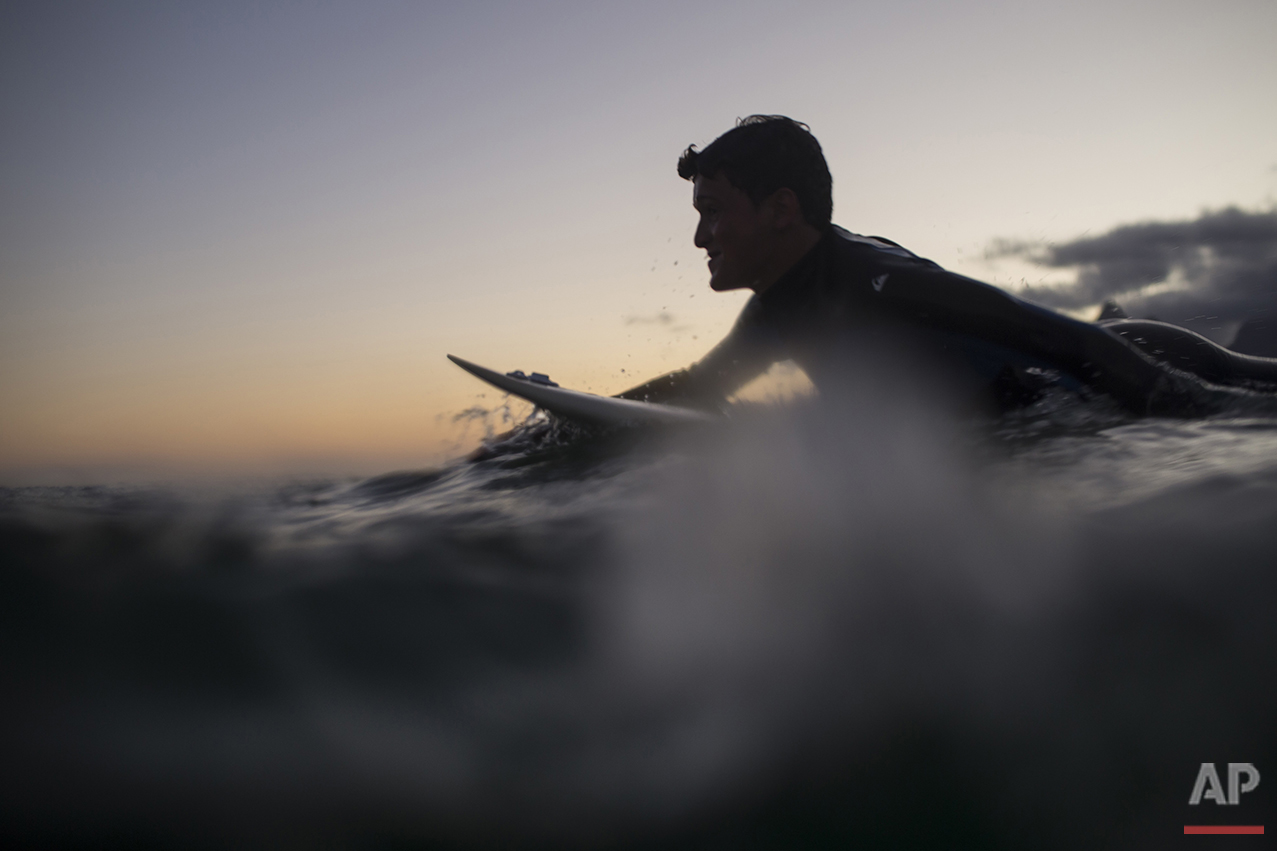 A surfer paddles on his board during sunset off Arpoador beach in Rio de Janeiro, Brazil, Saturday, Aug. 13, 2016. Long frowned upon as a counterculture movement or a mere pastime, surfing has spread around the world as a professional sport and multi-billion dollar industry. This month, the IOC included surfing in its Olympic program for the Tokyo Games in 2020, inspiring Rio's children who have heard about the athletes competing not far away from their beach. (AP Photo/Felipe Dana)