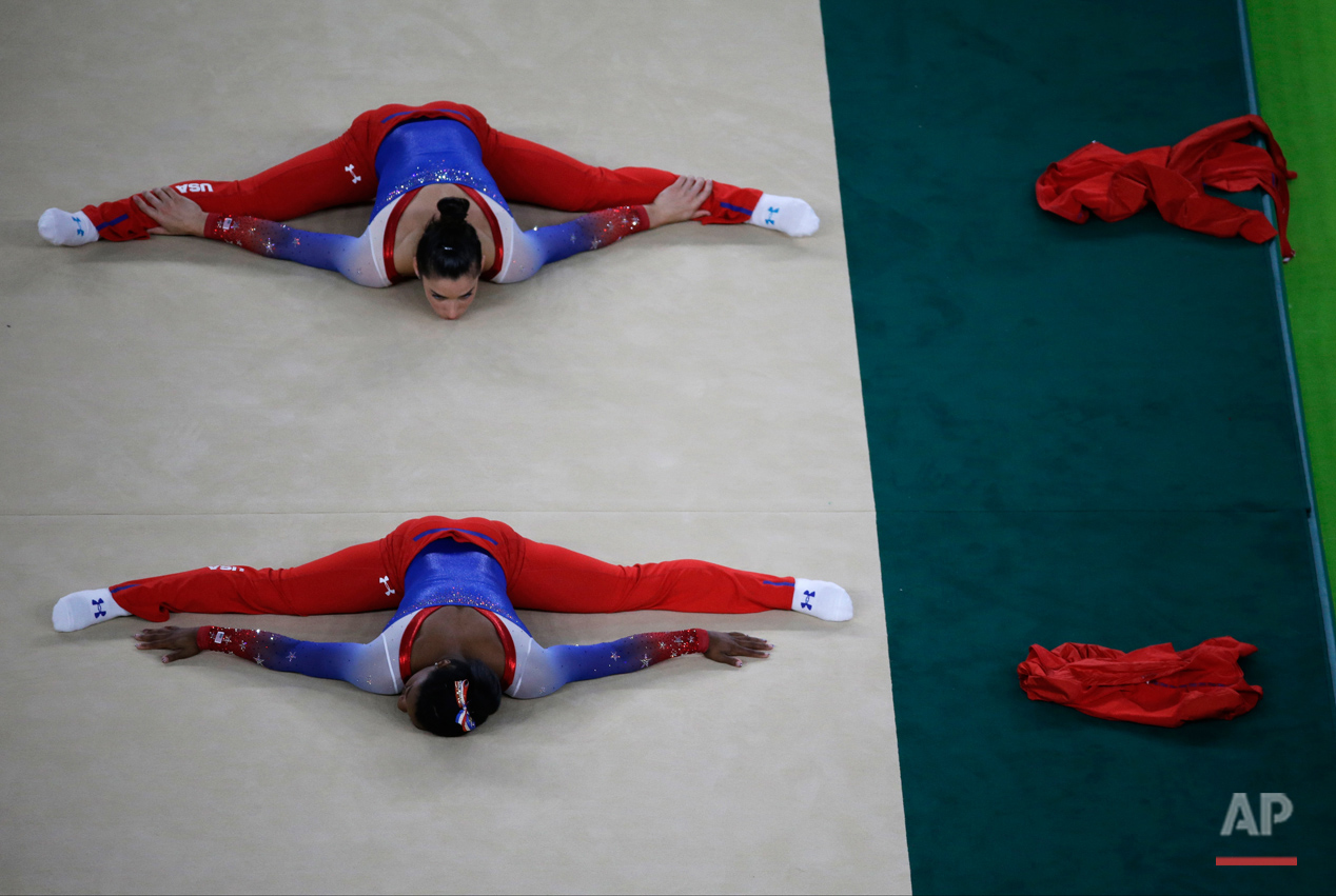 United States' Simone Biles, bottom, and compatriot Aly Raisman warm up before the start of the artistic gymnastics women's apparatus final at the 2016 Summer Olympics in Rio de Janeiro, Brazil, Tuesday, Aug. 16, 2016. (AP Photo/Rebecca Blackwell)