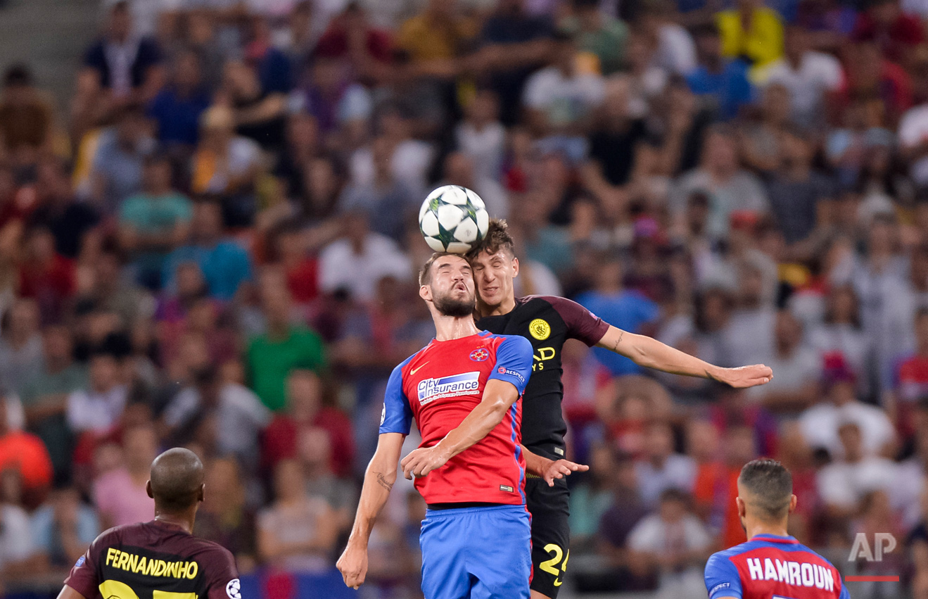 Manchester City's John Stones, right, vies with Steaua's Alexandru Tudorie, left, during the Champions League qualifying playoffs first leg soccer match at the National Arena Stadium in Bucharest, Romania, Tuesday, Aug. 16, 2016. (AP Photo/Andreea Alexandru)