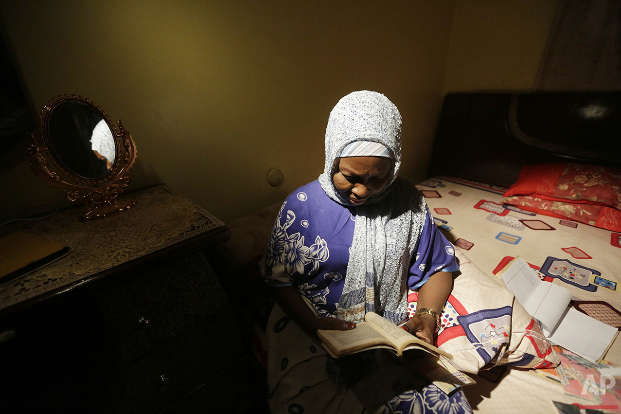 In this photo taken Tuesday April 5, 2016, author Hadiza Nuhu Gudaji reads through one of her novels in her bedroom in Kano, Nigeria. In the local market, stalls are signs of a feminist revolution with piles of poorly printed books by women, as part of a flourishing literary movement centered in the ancient city of Kano, that advocate against conservative Muslim traditions such as child marriage and quick divorces.  Dozens of young women are rebelling through romance novels, many hand-written in the Hausa language, and the romances now run into thousands of titles.  (AP Photo/Sunday Alamba)
