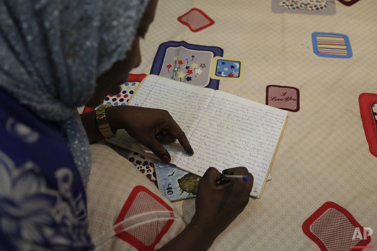 In this photo taken Tuesday April 5, 2016, author Hadiza Nuhu Gudaji composes a novel while resting on her bed with an exercise book and a ballpoint pen in Kano, Nigeria. In the local market, stalls are signs of a feminist revolution with piles of poorly printed books by women, as part of a flourishing literary movement centered in the ancient city of Kano, that advocate against conservative Muslim traditions such as child marriage and quick divorces. (AP Photo/Sunday Alamba)