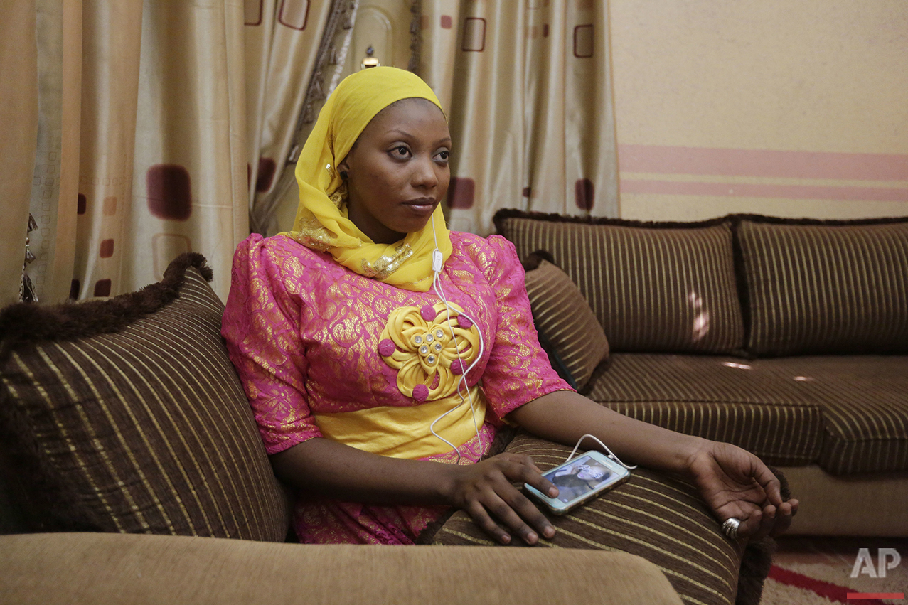 In this photo taken Tuesday, April 5, 2016, Khadija Gudaji, a Physics student at Northwest University, listens to a daily radio talk show on her mobile phone in Kano, Nigeria. In the local market, stalls are signs of a feminist revolution with piles of poorly printed books by women, as part of a flourishing literary movement centered in the ancient city of Kano, that advocate against conservative Muslim traditions such as child marriage and quick divorces. Dozens of young women are rebelling through romance novels, many hand-written in the Hausa language, and the romances now run into thousands of titles.  (AP Photo/Sunday Alamba)
