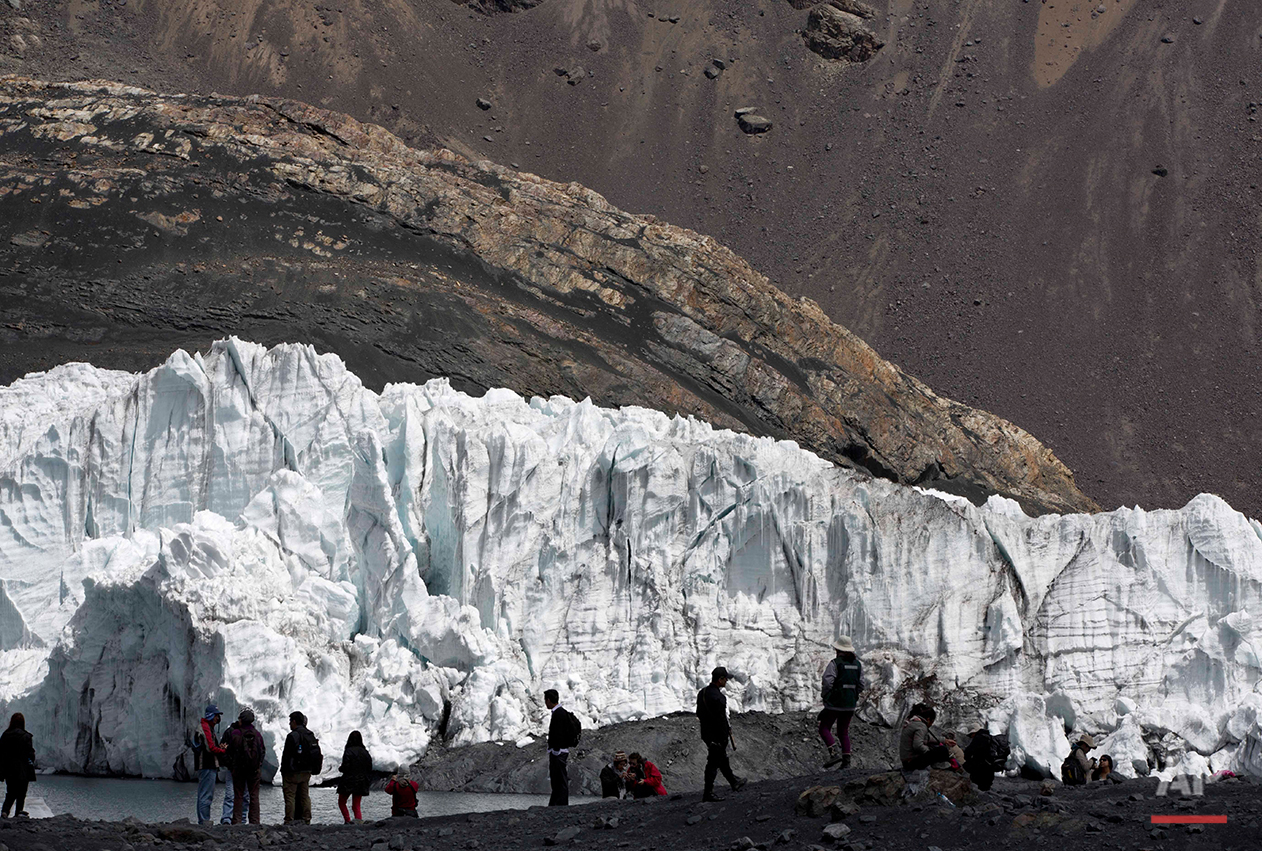 "In this Aug. 12, 2016 photo, a group of tourists walk in front of the Pastoruri glacier in a tour called ""The Route of Climate Change"" in Huaraz, Peru. The melting of glaciers like the Pastoruri has put cities like Huaraz, located downslope from the glacier about 35 miles (55 kilometers) away, at risk from what scientists call a ""glof,"" or glacial lake outburst flood. A glof occurs when the weak walls of a mountain valley collapse under the weight of meltwater from a glacier. (AP Photo/Martin Mejia)"