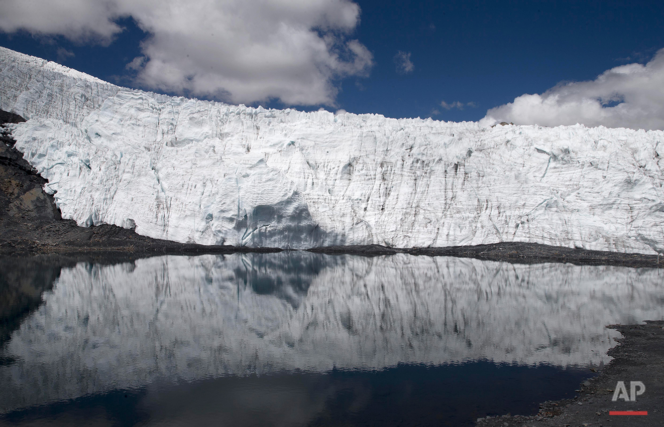 In this Aug. 12, 2016 photo, the Pastoruri glacier is reflected in a lagoon in the Huascaran National Park in Huaraz, Peru. Glacial lakes are often pretty fragile structures, created when rocks and rubble carried by a glacier form a moraine that dams up its water outflow. The dam can also be created by chunks of a glacier's own ice. These inherently unstable structures can collapse quickly, especially in places like Peru that are prone to frequent, violent earthquakes. (AP Photo/Martin Mejia)