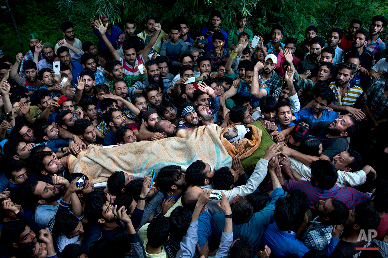 Kashmiri villagers carry body of Burhan Wani, chief of operations of Indian Kashmir's largest rebel group Hizbul Mujahideen, during his funeral procession in Tral, some 38 Kilometers (24 miles) south of Srinagar, Indian controlled Kashmir, Saturday, July 9, 2016. Indian troops fired on protesters in Kashmir as tens of thousands of Kashmiris defied a curfew imposed in most parts of the troubled region Saturday and participated in the funeral of the top rebel commander killed by Indian government forces, officials and locals said. (AP Photo/Dar Yasin)