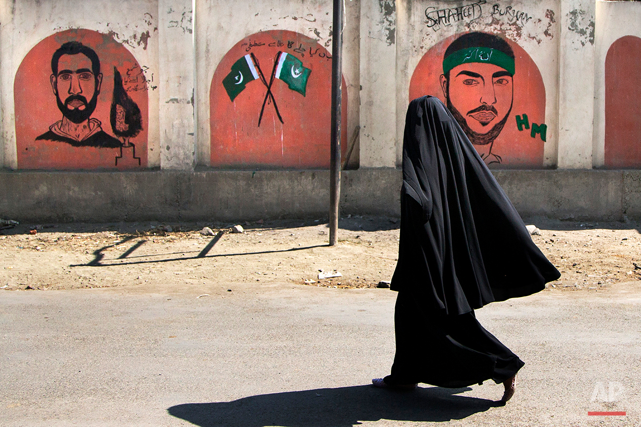 A burqa-clad woman walks past graffiti of Burhan Wani, right, a top rebel commander and a civilian who was killed earlier this month during curfew in Srinagar, Indian-controlled Kashmir, Friday, Aug. 12, 2016. Curfew and protests have continued across the valley amidst outrage over the killing of a top rebel leader by Indian troops in early July, 2016. (AP Photo/Dar Yasin)
