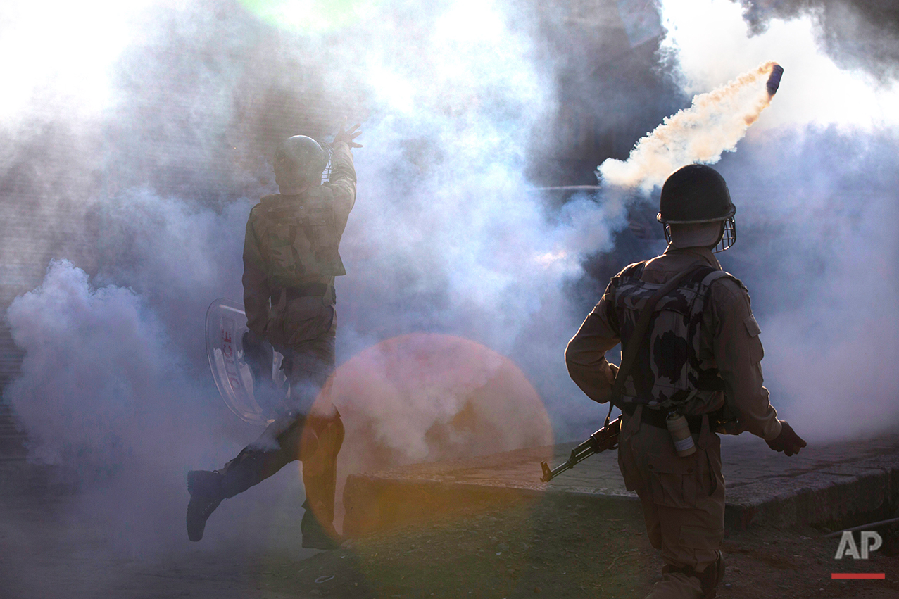 Indian paramilitary soldier throws exploded tear gas shell at Kashmiri Muslim protesters during a protest at the end of day long curfew in Srinagar, Indian controlled Kashmir, Friday, Aug. 12, 2016. Curfew and protests have continued across the valley amidst outrage over the killing of a top rebel leader by Indian troops in early July, 2016. The red spot on the image is due to lens flare. (AP Photo/Dar Yasin )