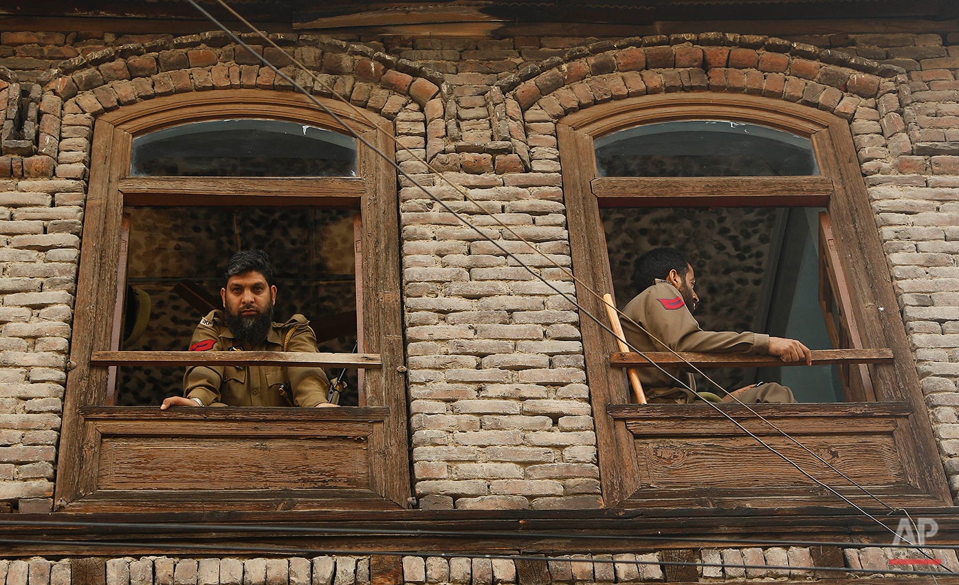Indian policemen keep guard from the window of a residential house during curfew in Srinagar, Indian controlled Kashmir, Wednesday, July 13, 2016. Curfew imposed in the disputed Himalayan region continues for the fifth consecutive day to suppress anti-India violence following the Friday killing of Burhan Wani, chief of operations of Hizbul Mujahideen, Kashmir's largest rebel group. ( AP Photo/Mukhtar Khan)