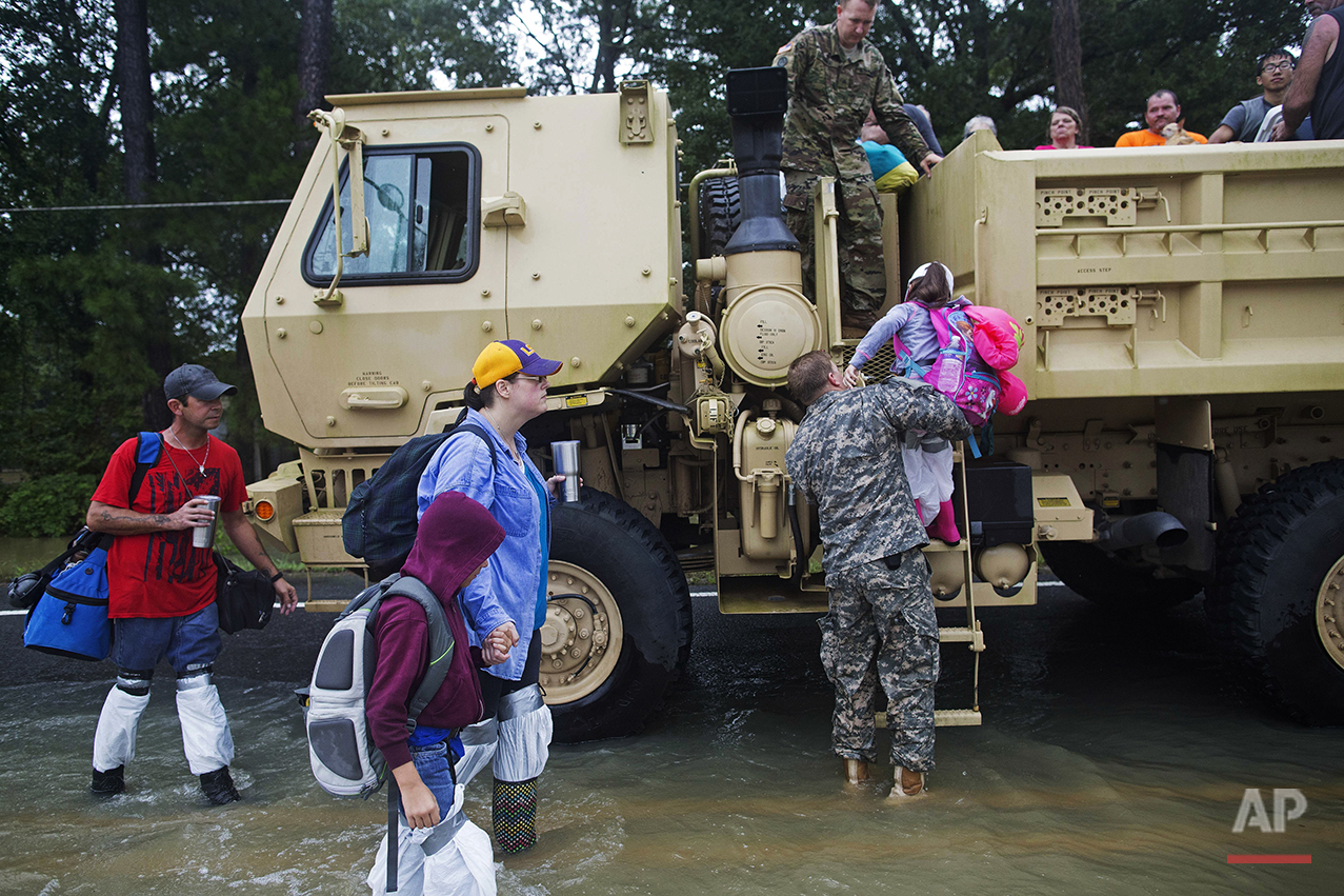 Kevin Richmond, left, and Barbara Manuel and her two children Elliott, 8, center, and Emily, 5, right, are rescued by members of the Louisiana Army National Guard from rising floodwater near Walker, La., after heavy rains inundated the region, Sunday, Aug. 14, 2016. (AP Photo/Max Becherer)