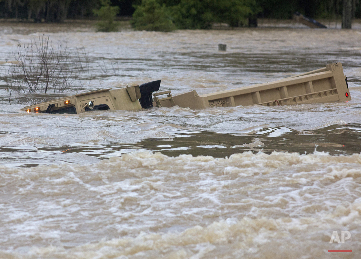 In this Sunday, Aug. 14, 2016 photo, a Louisiana Army National Guard dump truck that drove off the road is submerged in flood waters near Walker, La., after heavy rains inundated the region, (AP Photo/Max Becherer)