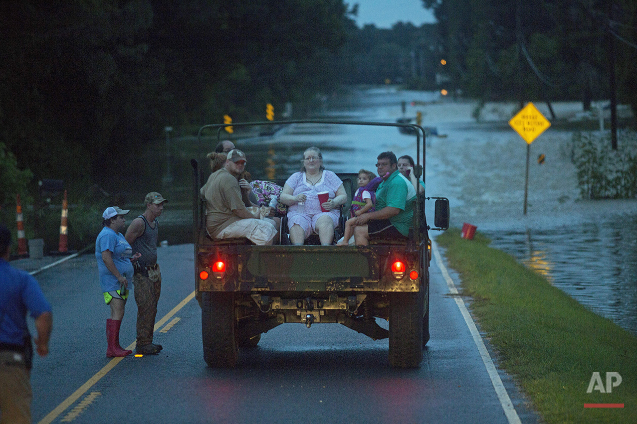 In tis Sunday, Aug. 14, 2016 photo, flood victims are rescued by emergency responders from near Walker, La., after heavy rains inundated the region. (AP Photo/Max Becherer)