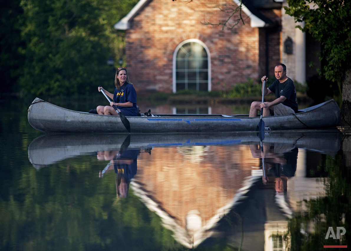 Danny and Alys Messenger paddle a canoe away from their home after reviewing flood damage in Prairieville, La., Tuesday, Aug. 16, 2016. Flooding prompted more than 30,000 rescues and left an estimated 40,000 homes damaged in south Louisiana. (AP Photo/Max Becherer)