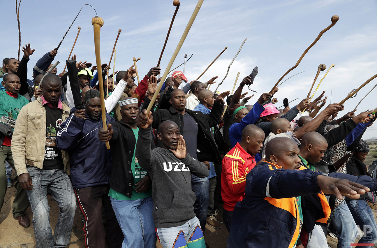 Mine workers sing as they wait for the start of commemoration ceremonies near Marikana in Rustenburg, South Africa, Tuesday, Aug. 16, 2016. On Aug. 16, 2012, police shot and killed 34 Lonmin striking miners, apparently while trying to disperse them and end their strike. Ten people, including two police officers and two Lonmin security guards, were killed in the preceding week. (AP Photo/Themba Hadebe)