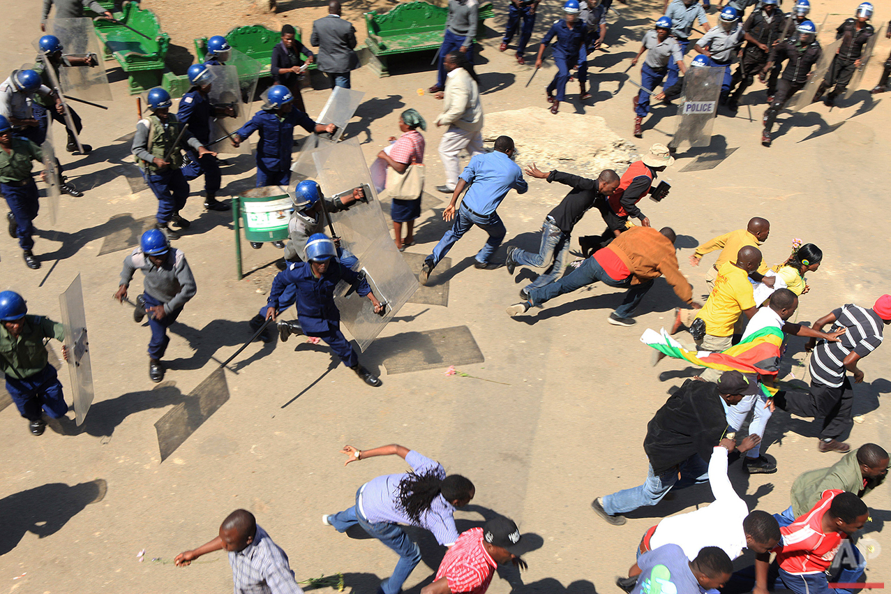 Riot police clash with protestors during a demonstration against the introduction of bond notes by the Reserve Bank of Zimbabwe, in Harare, Wednesday, Aug. 17, 2016. Several protestors were beaten as they took to the streets in a peaceful demonstration aimed at venting their anger and frustrations at the imminent introduction of the notes, which the country's Central Bank says will be equivalent to the United States dollar. (AP Photo/Tsvangirayi Mukwazhi)