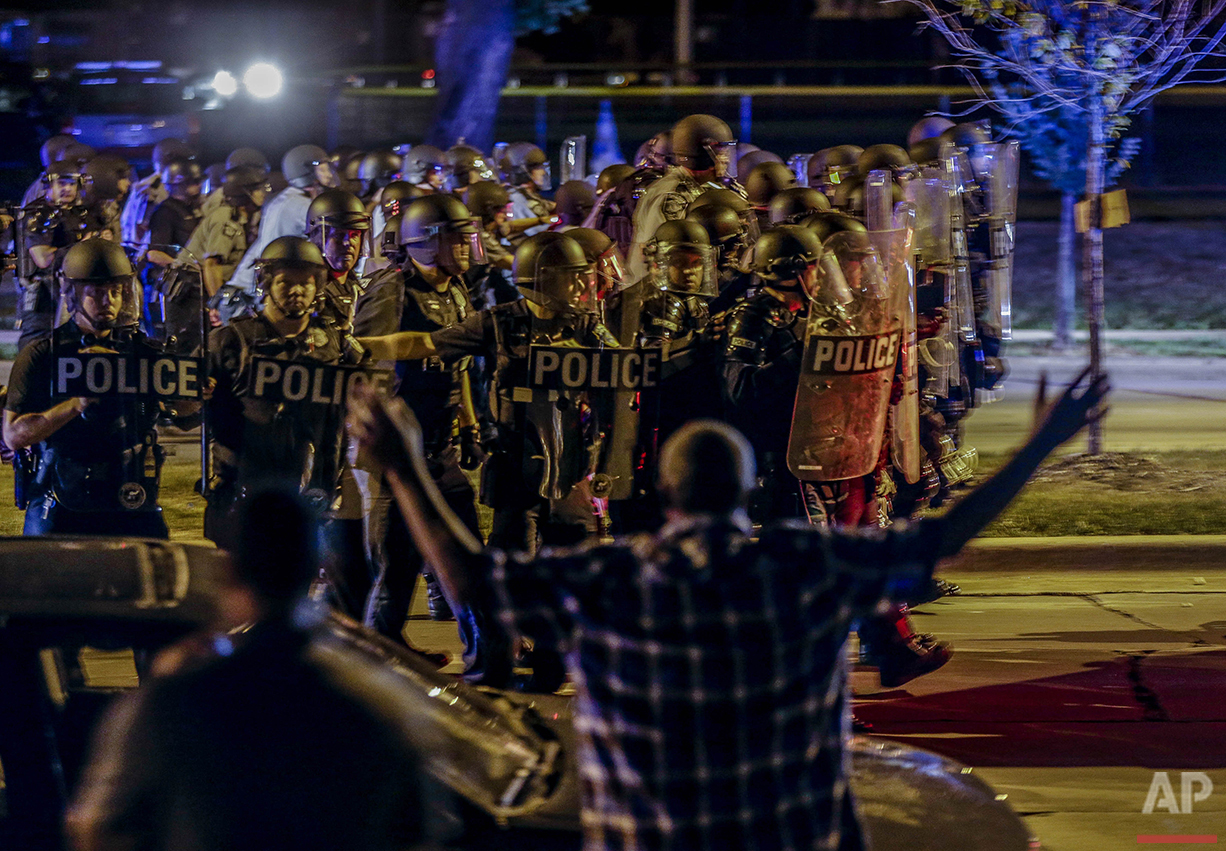 Police move in on a group of protesters throwing rocks at them in Milwaukee, Sunday, Aug. 14, 2016. A black man, whose death at the hands of police spurred two nights of violence in Milwaukee, was shot once in the chest and once in the arm, the Milwaukee County medical examiner said Friday. (AP Photo/Jeffrey Phelps)