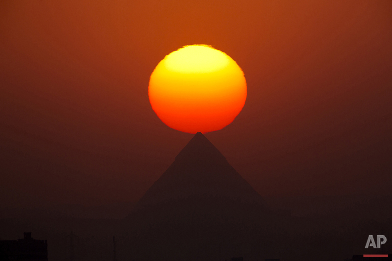 The sun sets behind the pyramids in Giza, Egypt, near Cairo on Friday, Aug. 19, 2016. (AP Photo/Amr Nabil)