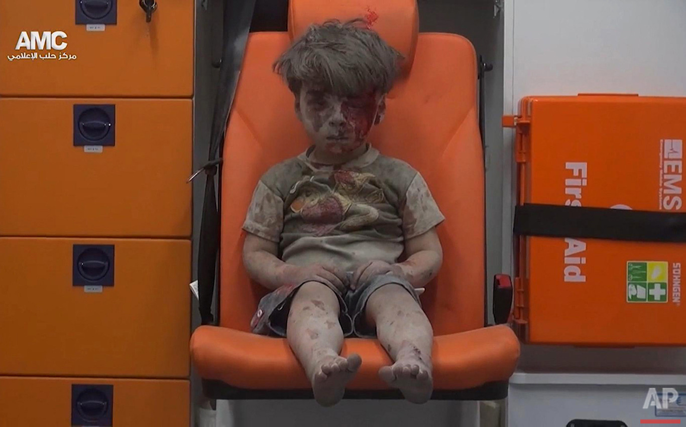 In this image made from video provided by the Syrian anti-government activist group Aleppo Media Center (AMC), a child sits in an ambulance after being pulled out of a building hit by an airstirke in Aleppo, Syria, Wednesday, Aug. 17, 2016. Syrian opposition activists reported an airstrike at the al-Qaterji neighborhood in Aleppo late Wednesday. (Aleppo Media Center via AP)