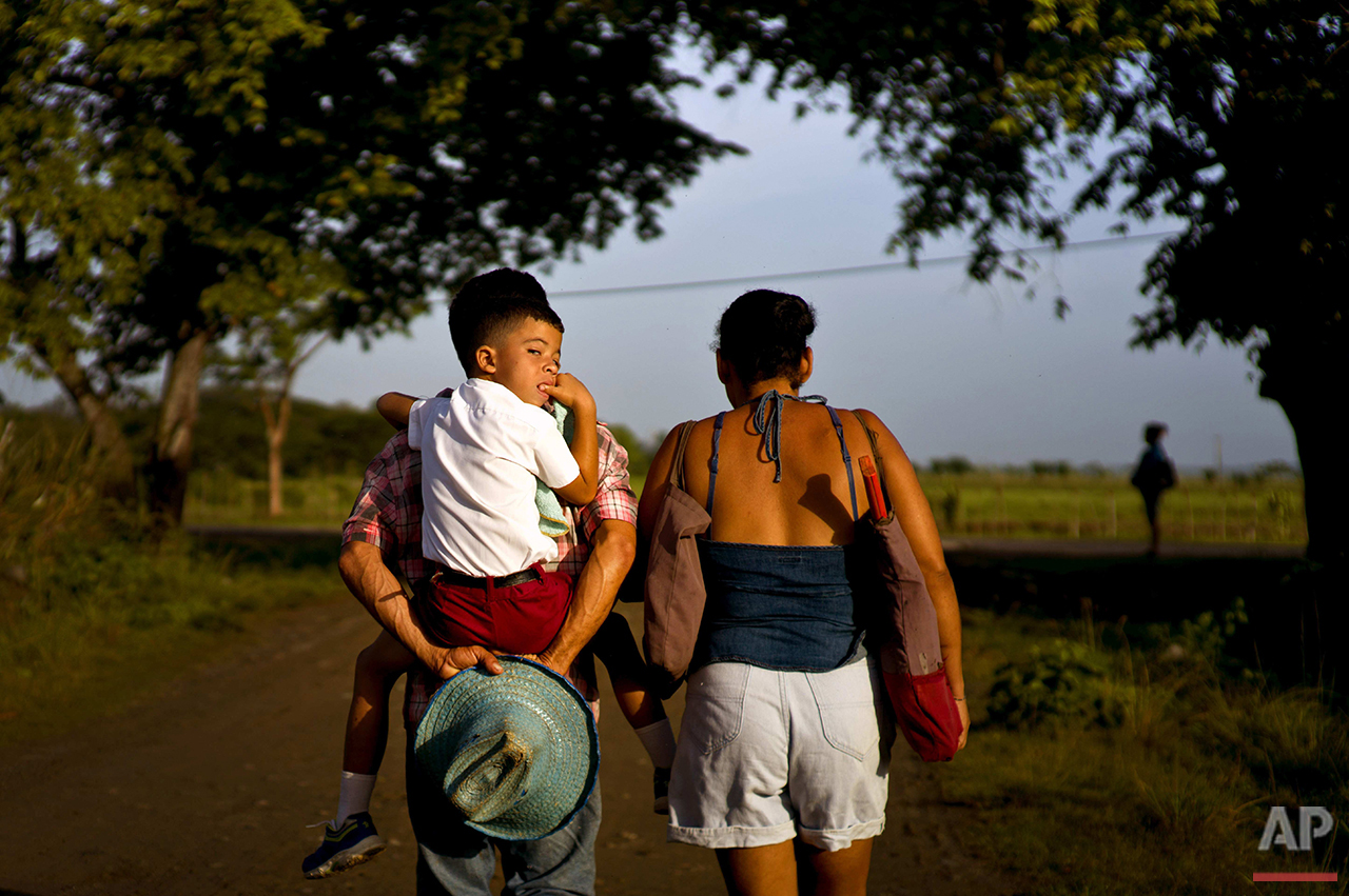 In this June 15, 2016 photo, four-year-old Kelvin Lopez Quintana gets an early morning piggyback ride to school from his father, along the road where the childhood home-turned-museum of Fidel Castro and his brother, President Raul Castro, is located Biran, Cuba. Fidel Castro spent only his early childhood living at his family's property in Biran before he was sent to boarding school in Santiago, though he often returned for vacations. (AP Photo/Ramon Espinosa)