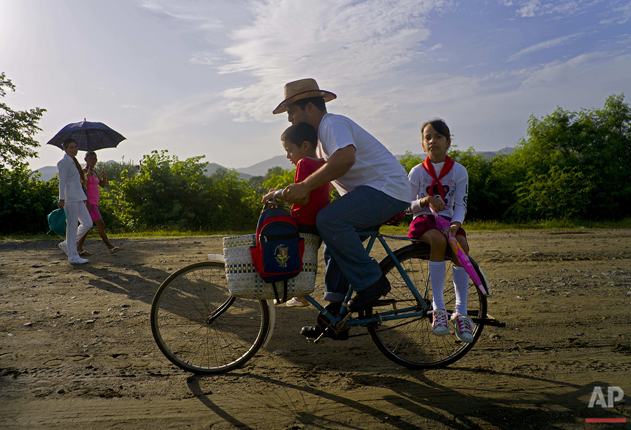 In this June 15, 2016 photo, Yosbani Rodriguez bikes his son Meiler and daughter Mayla to school before work in Biran, Cuba. Rodriguez, 33, works as the historian at the nearby home-turned-museum where Fidel Castro and his brother, current President Raul Castro, were born and grew up. (AP Photo/Ramon Espinosa)