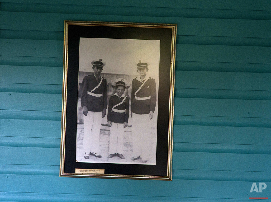 This June 10, 2016 photo shows a family photograph of the Castro brothers, from left, Fidel, Raul and Ramon, on the wall of the room they shared as children in Biran, Cuba. Since 2002, the site has been a museum, and it is gaining increasing attention in the run-up to Fidel Castro's 90th birthday on Aug. 13. (AP Photo/Ramon Espinosa)