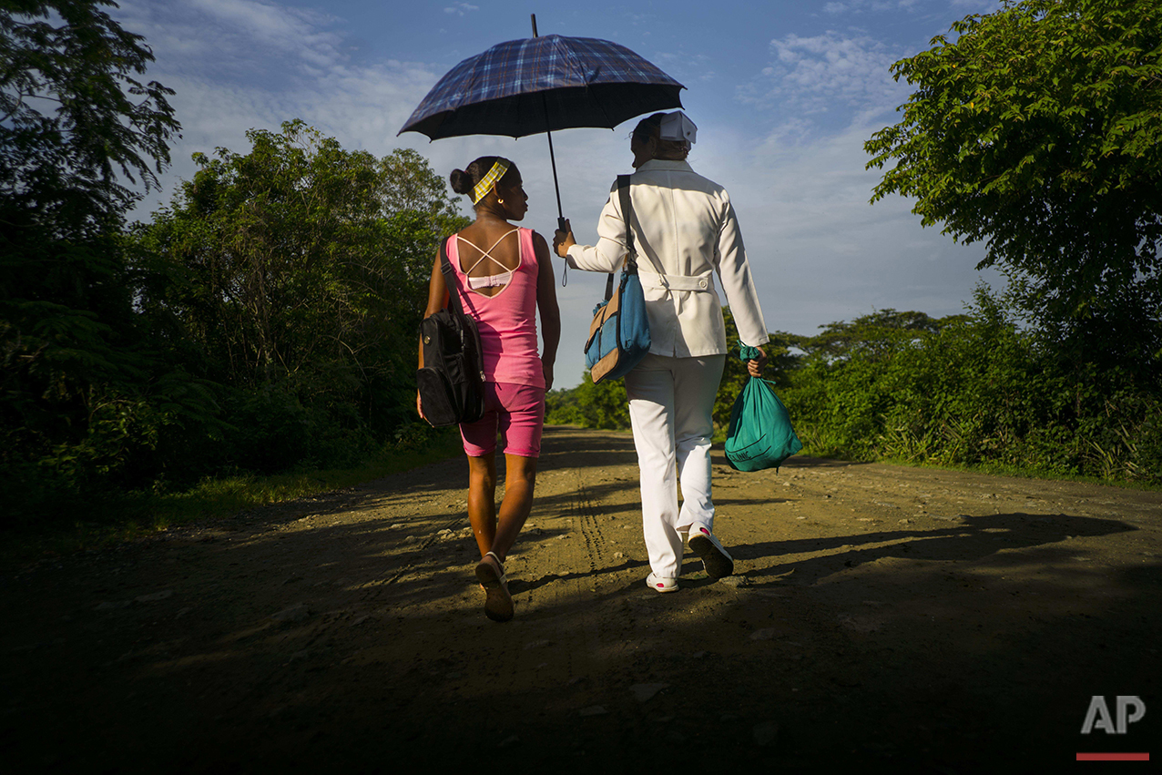 "In this June 15, 2016 photo, a nurse shades herself with an umbrella as she walks home after work with a friend near the home-turned-museum where Fidel Castro and his brother, president Raul Castro, were born in Biran, Cuba. Fidel Castro hasn't visited Biran since his childhood property was restored and quietly opened to the public in November 2002. Even the name of the place, ""The Biran Historic Site,"" makes no mention of Castro, who is among the most famous Latin American figures of the 20th century. (AP Photo/Ramon Espinosa)"