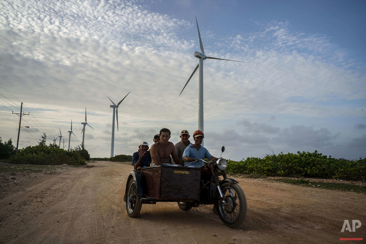 "In this June 11, 2016 photo, men commute on a motorcycle with sidecar, driving past wind turbines along the way in Gibara, in Cuba's Holguin province where Fidel Castro was born and grew up. ""There is no cult of personality around any living revolutionary in the form of statues, official photographs or the names of streets or institutions,"" Castro said in his 2003 May Day speech. ""The leaders of this country are human beings, not gods."" (AP Photo/Ramon Espinosa)"