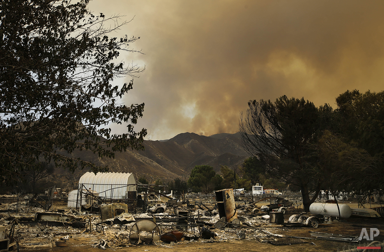 Smoke rises over a mountain behind the remains of mobile homes devastated by a wildfire in South Lake, Calif., on Saturday, June 25, 2016. (AP Photo/Jae C. Hong)