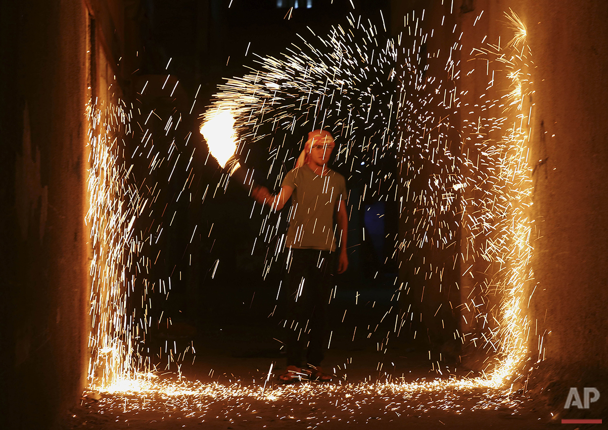 A Palestinian youth plays with fireworks as he celebrates the Muslim holy month of Ramadan in the alley in Jebaliya refugee camp, Gaza Strip, early Sunday, June 26, 2016. Ramadan is traditionally a time of reflection and prayer, and Muslims are expected to abstain during daylight hours from food, drink, smoking and sex and to focus on spirituality, good deeds and charity. (AP Photo/Adel Hana)