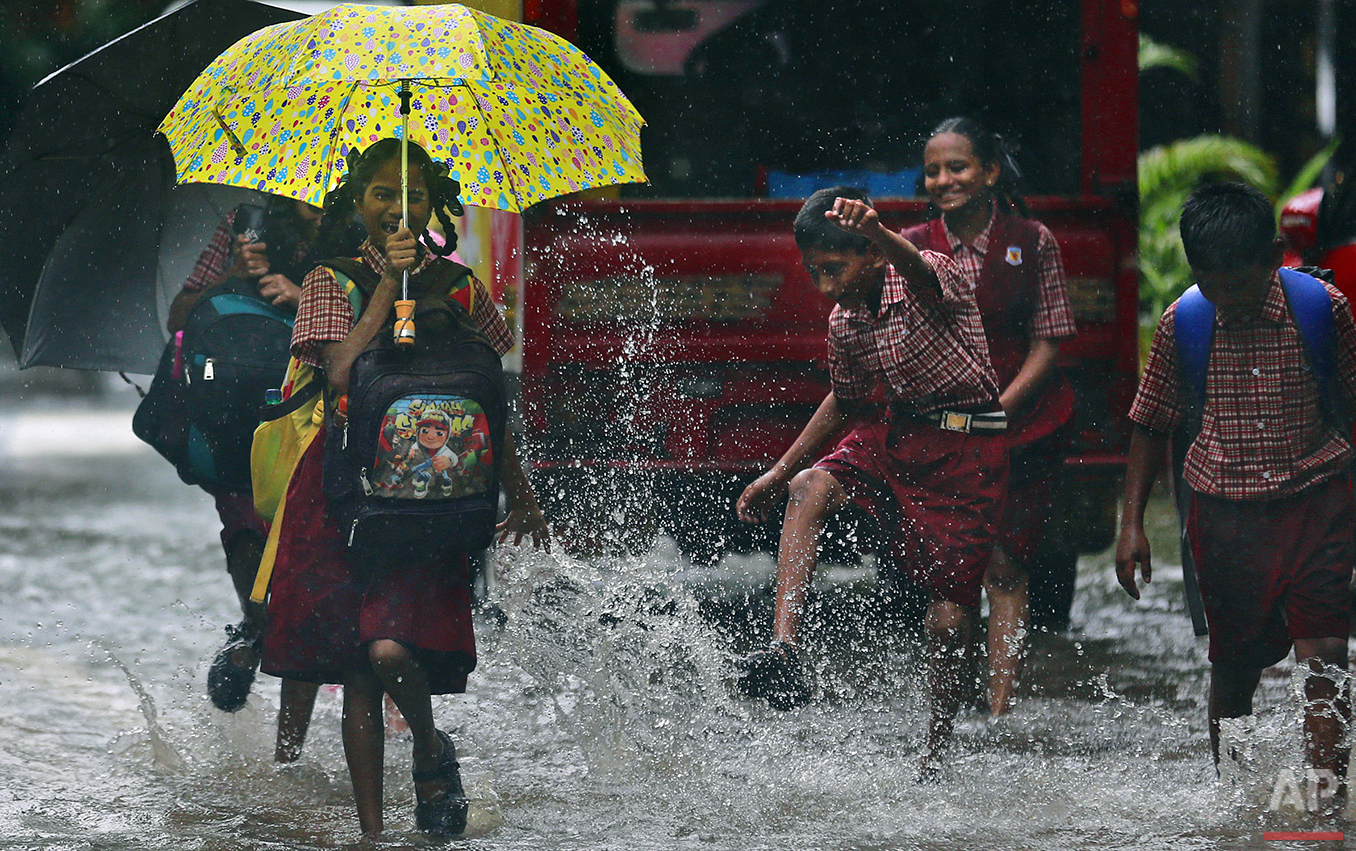 A girl reacts to a boy splashing water on her on a flooded street in Mumbai, India, Tuesday, June 28, 2016. India's monsoon season runs from June to September. (AP Photo/Rafiq Maqbool)