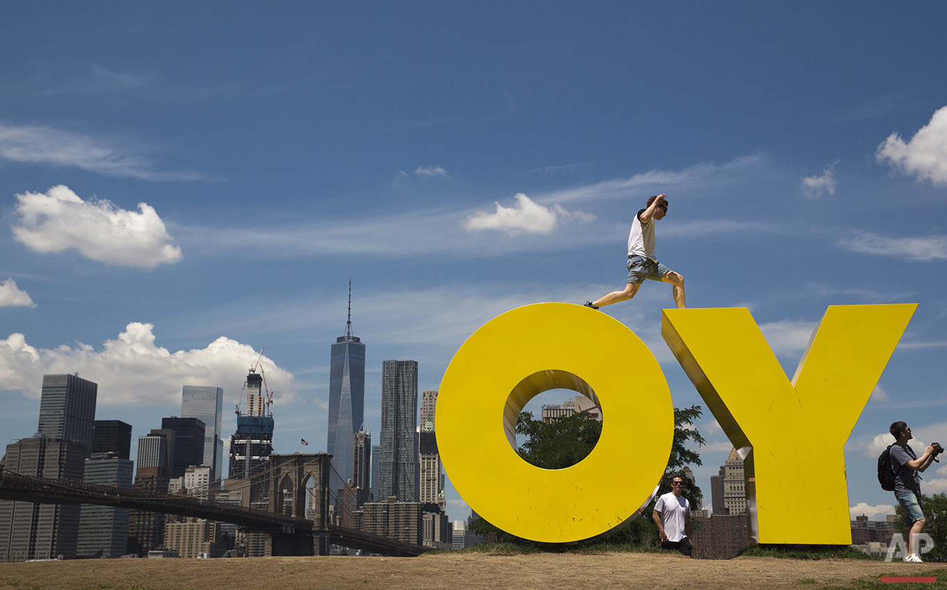 A visitor to the Brooklyn Bridge park jumps between the letters in Deborah Kass' sculpture OY/YO in New York on Thursday, June 30, 2016. (AP Photo/Mary Altaffer)