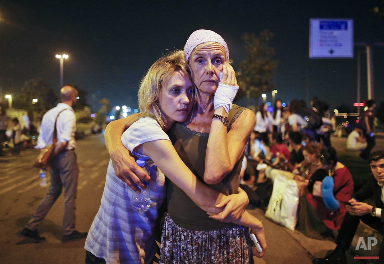 Passengers embrace each other as they wait outside Istanbul's Ataturk airport, early Wednesday, June 29, 2016 following their evacuation after a blast. Suspected Islamic State group extremists have hit the international terminal of Istanbul's Ataturk airport, killing dozens, Turkish officials said Tuesday. Turkish authorities have banned distribution of images relating to the Ataturk airport attack within Turkey. (AP Photo/Emrah Gurel)