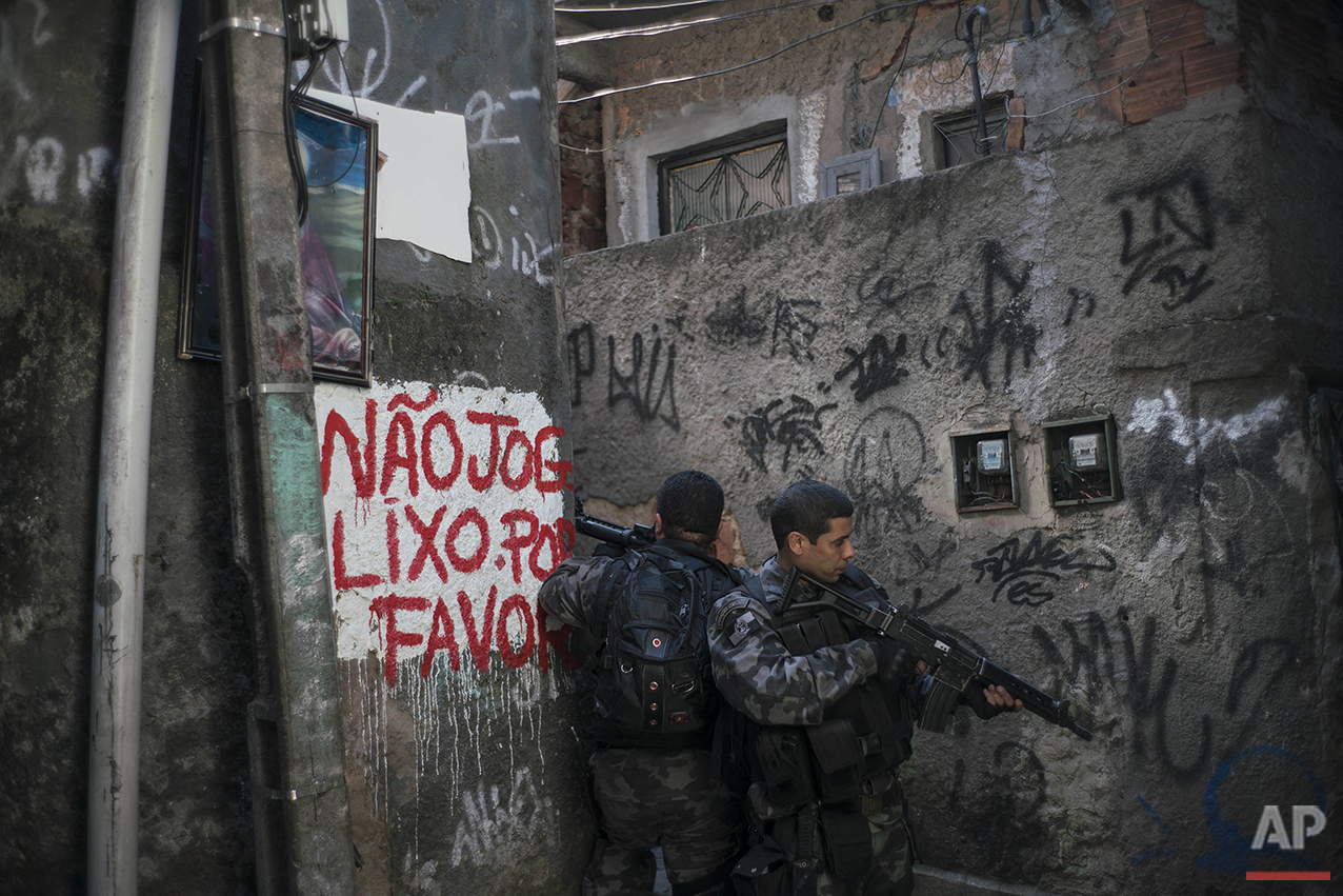 Officers take positions during a police operation against drug traffickers in the Jacarezinho slum of Rio de Janeiro, Wednesday, June 29, 2016. Recent violence is adding to worries about safety in Rio during the Olympics. Officials have warned that budget shortfalls may compromise security during the games. (AP Photo/Felipe Dana)