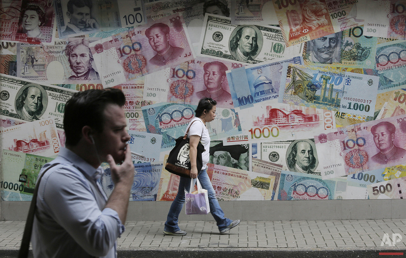Pedestrians walk past a money exchange shop decorated with different bank notes in Hong Kong, Monday, June 27, 2016. (AP Photo/Vincent Yu)