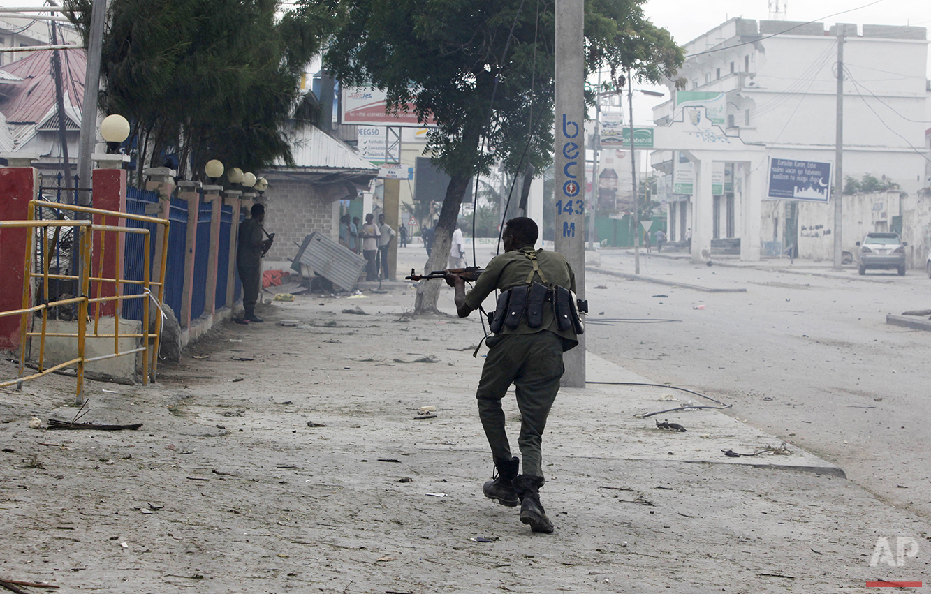 """A Somali soldier takes position during an attack on the Nasahablod Hotel in Mogadishu, Somalia on Saturday, June 25, 2016. Gunmen stormed the hotel, taking guests hostage and """"shooting at everyone they could see,"""" before security forces pursued the grenade-throwing assailants to the top floor and ended the hours-long deadly assault, police and witnesses said. (AP Photo/Farah Abdi Warsameh)"""