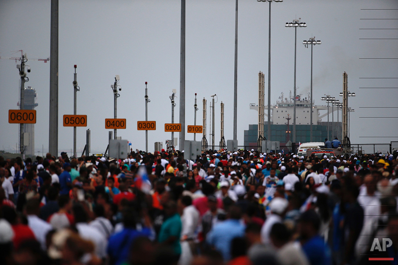 Thousands watch as the Neopanamax cargo ship, Cosco Shipping Panama, prepares to cross the new Agua Clara locks, part of the Panama Canal expansion project, near the port city of Colon, Panama, Sunday June 26, 2016. The ship, carrying more than 9,000 containers, entered the newly expanded locks that will double the Panama Canal's capacity in a multibillion-dollar bet on a bright economic future despite tough times for international shipping. (AP Photo/Moises Castillo)