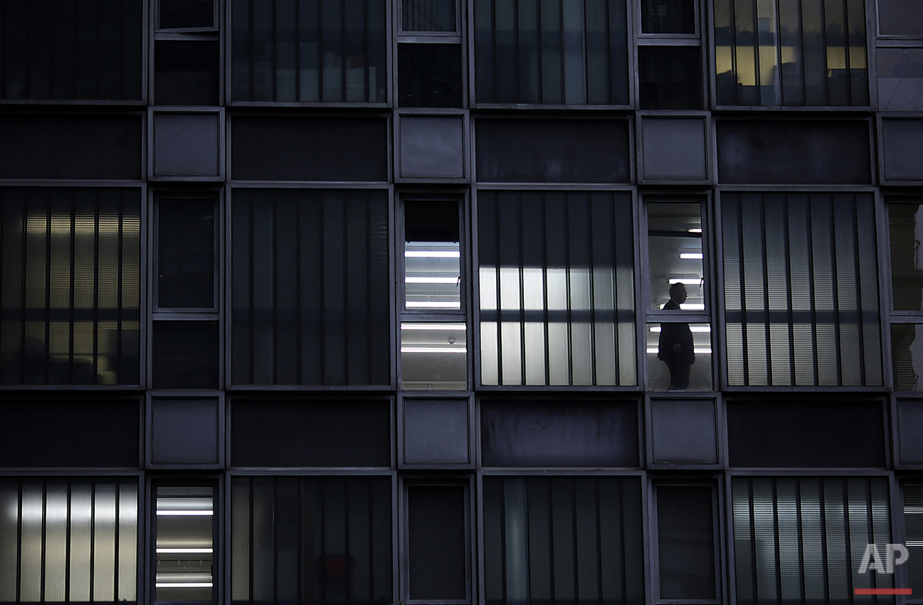 A man, in silhouette, walks through an office building in the Shimbashi district of Tokyo, Japan, Tuesday, June 28, 2016. Shimbashi is one of the largest commercial districts in Japan's capital city. (AP Photo/Eugene Hoshiko)