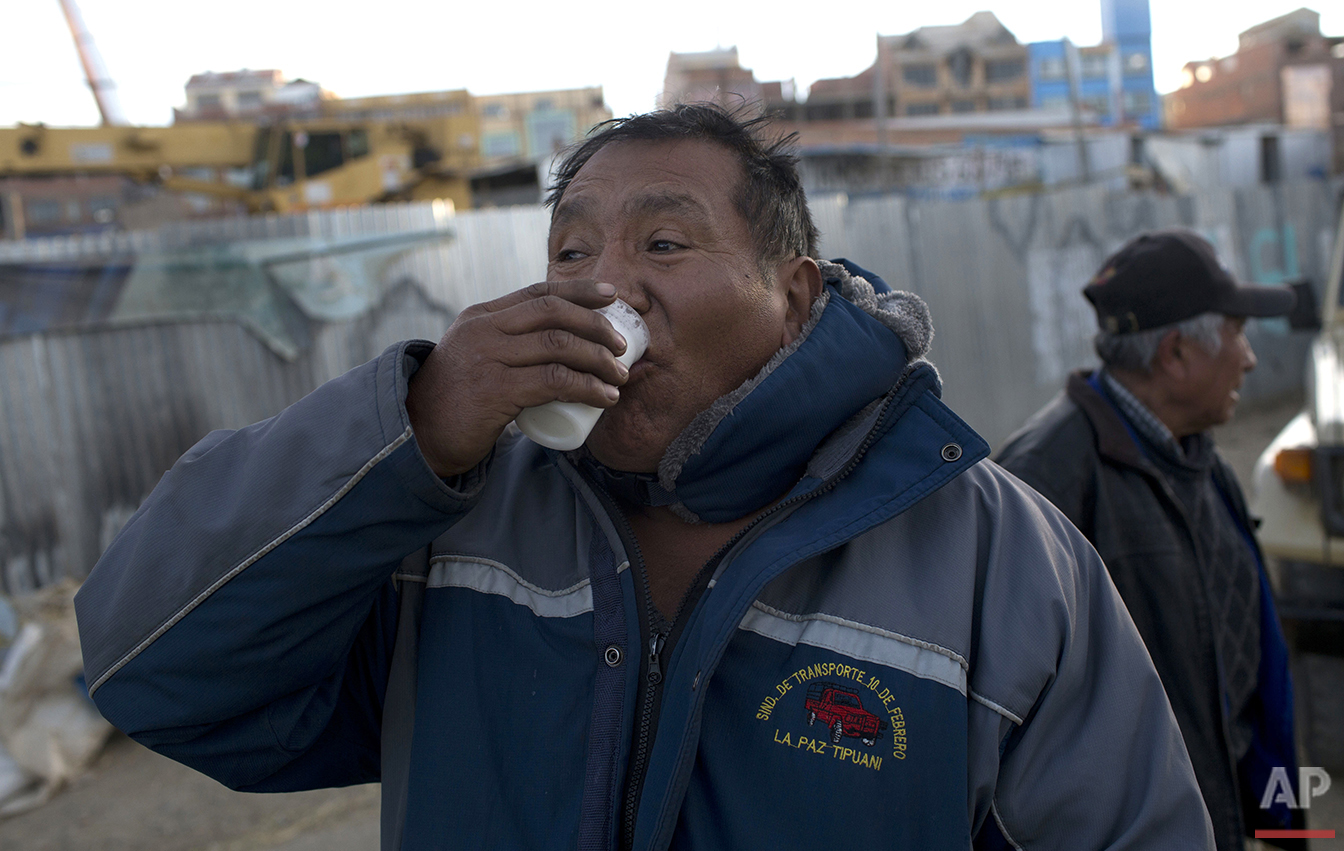 """In this June 8, 2016 photo, bus driver Luis Lari Huanca drinks a glass of donkey milk in El Alto, Bolivia. """"My fellow drivers advised me to drink donkey milk because I suffer lung and kidney pain,"""" Lari Huanca said. """"It's the third day. I hope it cures me like my friends said it would.""""  (AP Photo/Juan Karita)"""