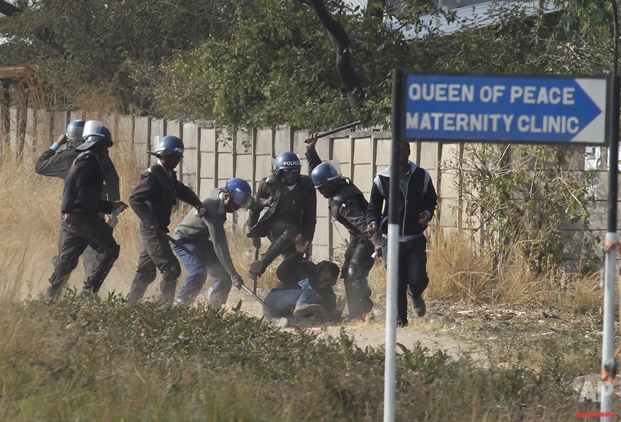 Armed police surround a rioter in Harare, Zimbabwe on Monday, July, 4, 2016. Police in the capital fired tear gas and water cannons in an attempt to quell rioting by taxi and mini bus drivers protesting what they describe as police harassment. The violence came amid a surge in protests in recent weeks because of economic hardships and alleged mismanagement by the government of President Robert Mugabe. (AP Photo/Tsvangirayi Mukwazhi)