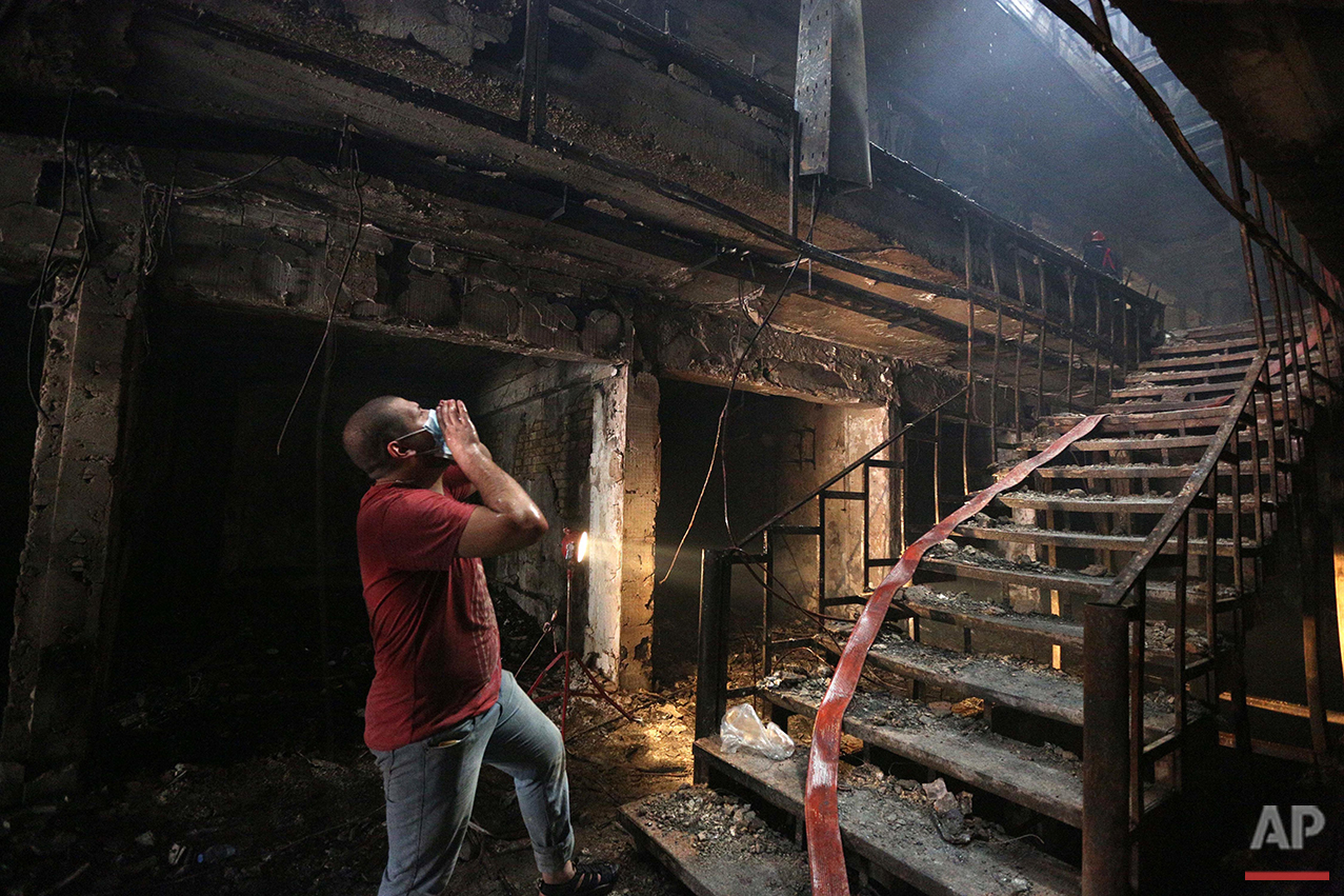 A man looks for victims at the site of a car bomb at a commercial area in the Karada neighborhood of Baghdad, Sunday, July 3, 2016. Hundreds were killed in two separate bomb attacks in and around the capital. The Islamic State group has claimed responsibility for both. (AP Photo/Hadi Mizban)