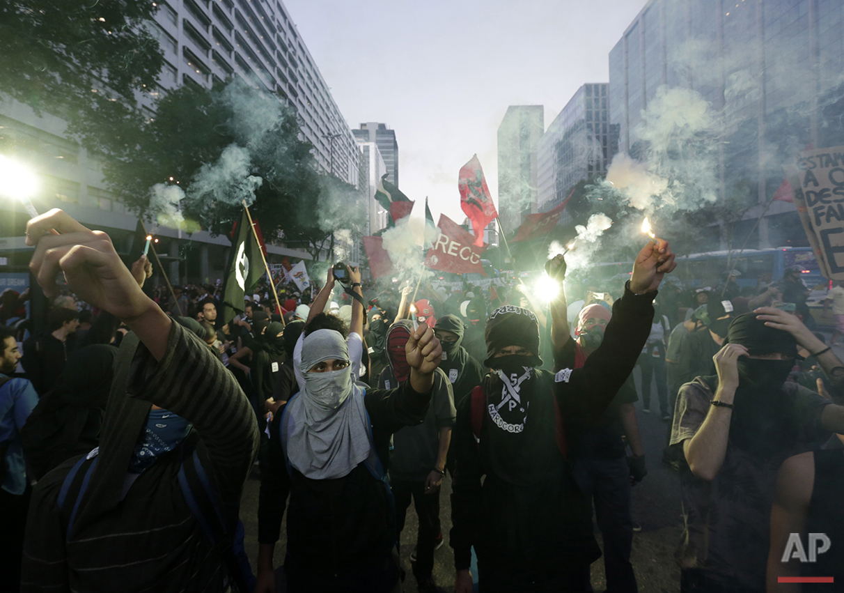 Students wearing masks burn flares during a protest demanding better education and protesting the money spent on the Olympics in Rio de Janeiro, Wednesday, July 6, 2016. With the Olympics set to start on Aug. 5, the games and the city have been overshadowed by security threats, violence, the Zika virus and a national political corruption scandal. (AP Photo/Silvia Izquierdo)