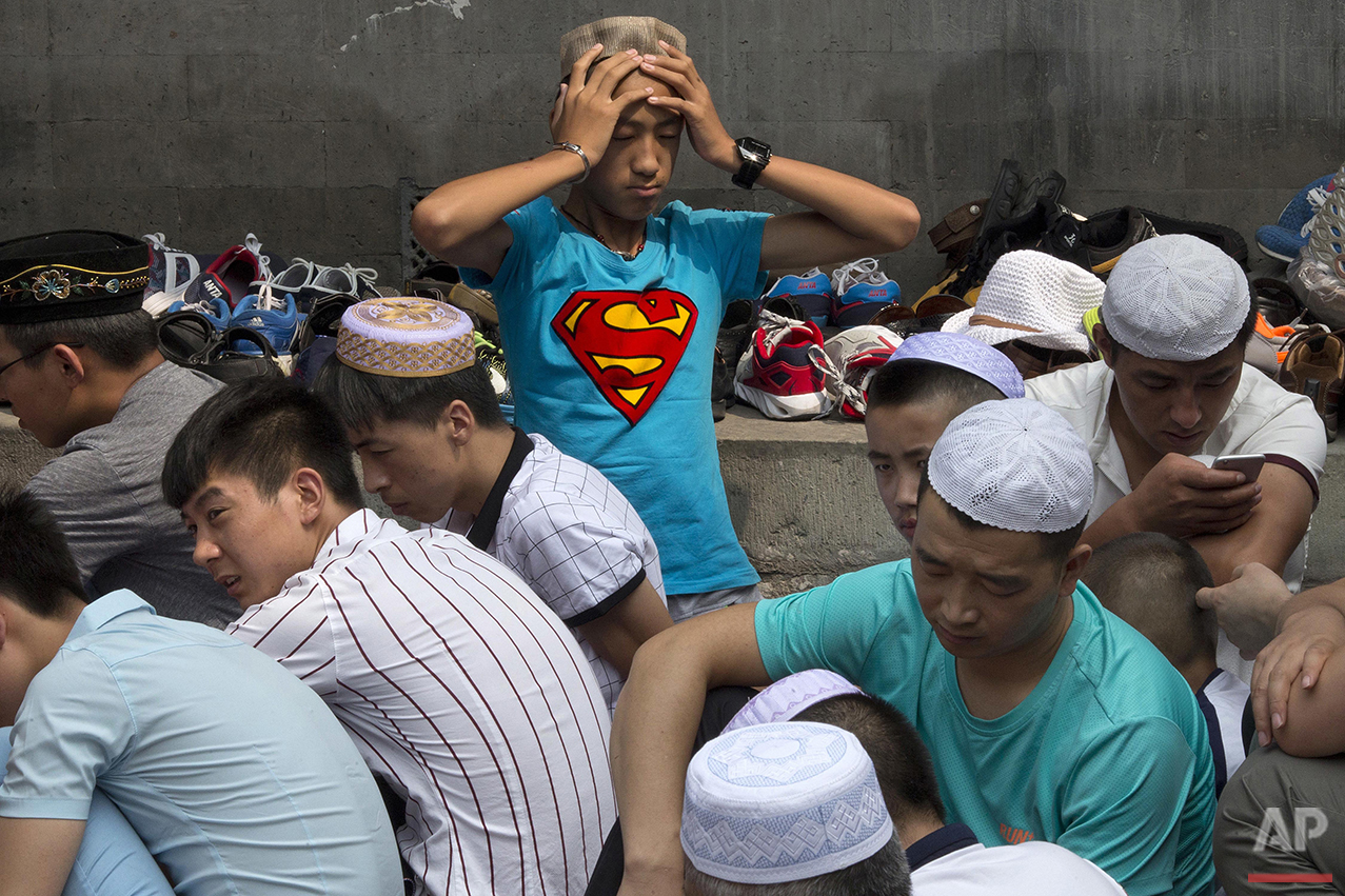 A man rubs his head during Eid al-Fitr prayers at the Niujie mosque, the oldest and largest mosque in Beijing, Wednesday, July 6, 2016. The Eid al-Fitr celebrations mark the end of the Muslim holy fasting month of Ramadan. (AP Photo/Ng Han Guan)