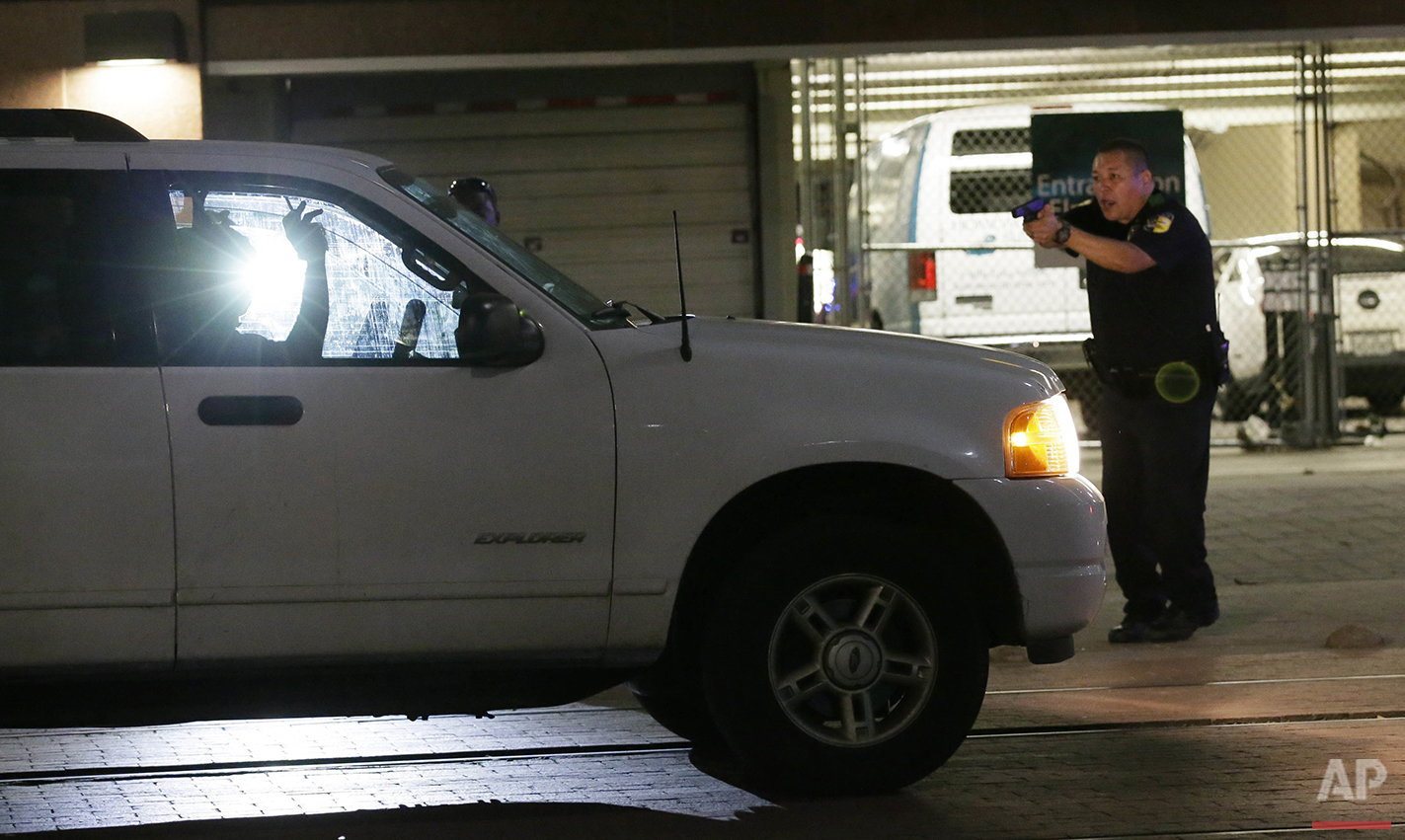 A police officer stops a driver in downtown Dallas on Thursday, July 7, 2016 after police officers were shot and killed during a protest over fatal police shootings of black men in other states. (AP Photo/LM Otero)