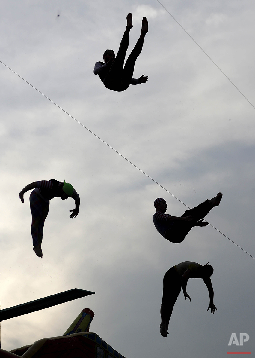 Divers jump into a 9.5-foot pool during a performance by the Sinbad High Dive Show at the State Fair Meadowlands carnival in East Rutherford, N.J., Thursday, July 7, 2016. (AP Photo/Julio Cortez)