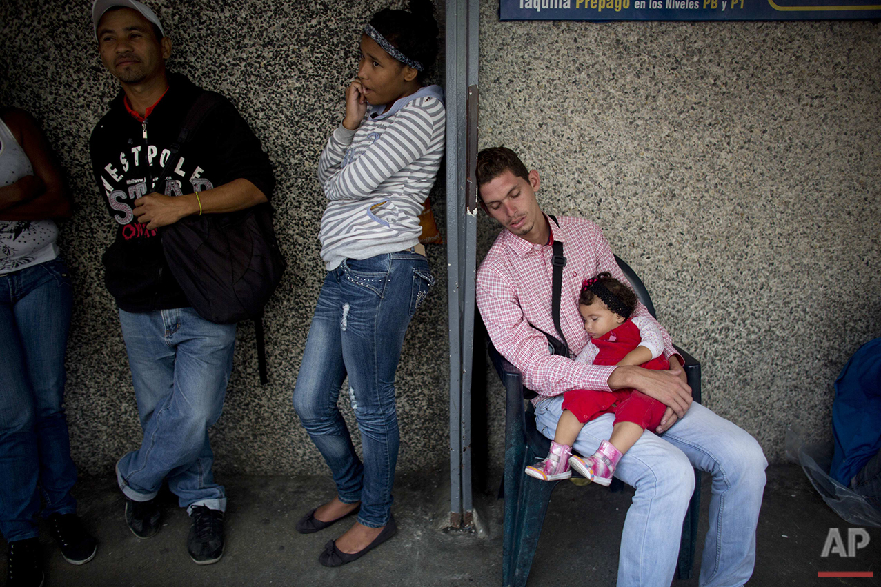 In this Tuesday, May 3, 2016 photo, people wait in line to buy food outside a supermarket in Caracas, Venezuela. Prices have been driven impossibly high by scarcity, hoarding and black market resellers, forcing Venezuelans to line up again and again for subsidized goods, not always knowing what they'll get when they finally reach the front. (AP Photo/Ariana Cubillos)