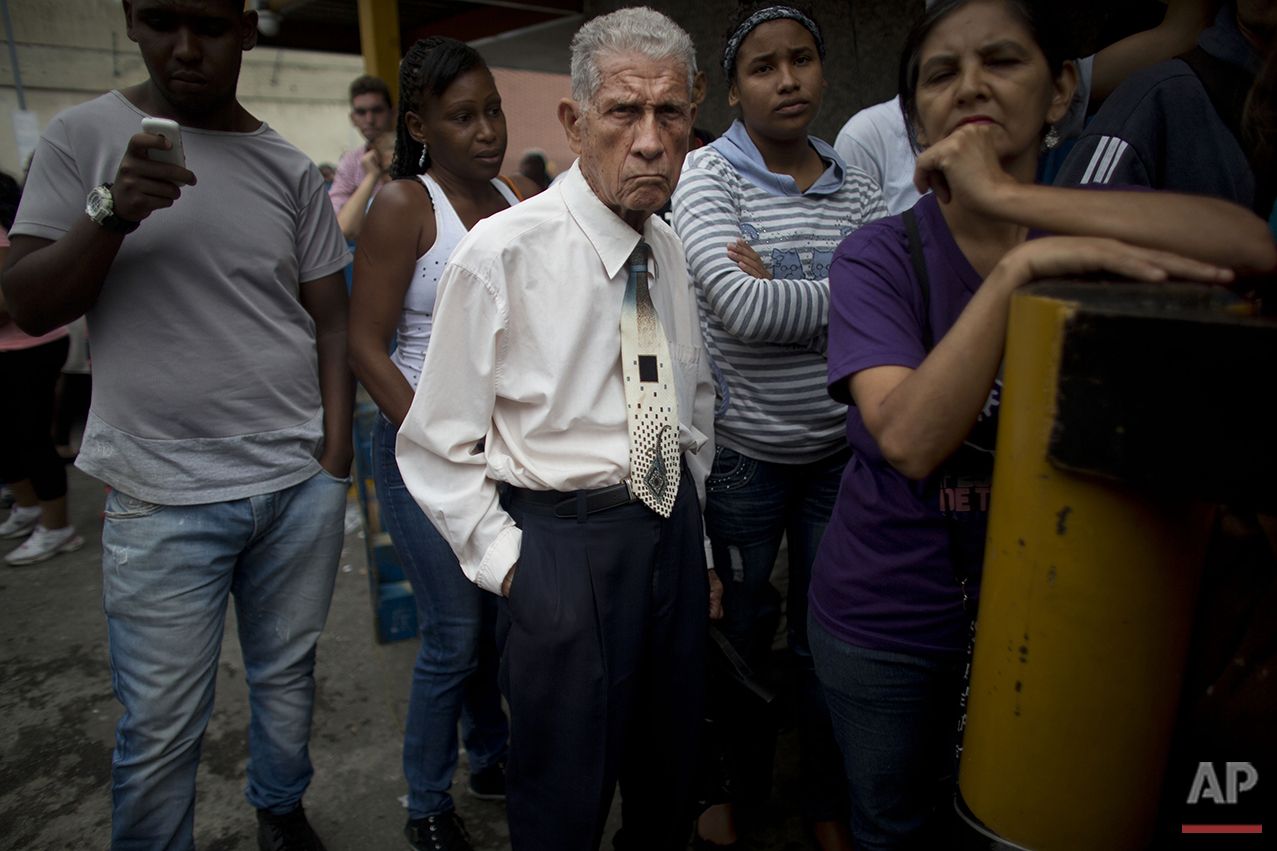 In this Tuesday, May 3, 2016 photo, people wait in line outside a supermarket to buy food in Caracas, Venezuela. The country's vast oil wealth once fueled a bustling economy, but years of government mismanagement ground much of the nation's production to a halt, and the country grew dependent on imports. (AP Photo/Ariana Cubillos)