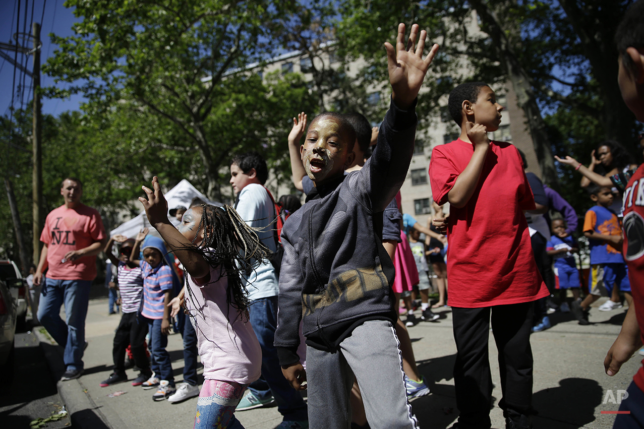 Children dance during an event in front of the Richmond Terrace housing in the Staten Island borough of New York, Thursday, June 9, 2016. On an island of 475,000 that is 75 percent white and mostly suburban, the North Shore's comparatively dense neighborhoods are home to nearly all of the borough's African-Americans, enclaves of Liberian, Mexican, and Sri Lankan immigrants. (AP Photo/Seth Wenig)