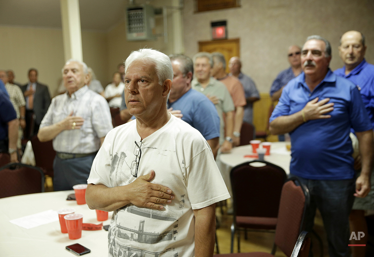 Members of the NYC Verrazano 10-13 Association, made up of retired police officers, say the Pledge of Allegiance during a meeting in the Staten Island borough of New York, Wednesday, June 15, 2016. One of the members can trace policing lineage from his grandfather's days as a bobby in northern England to his own son's promotion to detective in Brooklyn. Another recalls days on patrol when cops carried no radios. (AP Photo/Seth Wenig)
